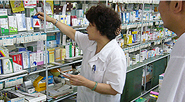 Staff in the pharmacy reaching for medicine at the counter
